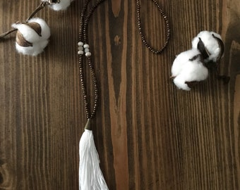 Brown and cream beaded necklace wih white tassel