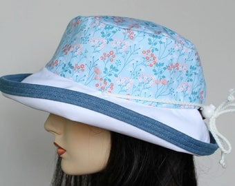Sunblocker UV summer sun hat with large wide brim featuring delicate floral in tones of blue and adjustable fit
