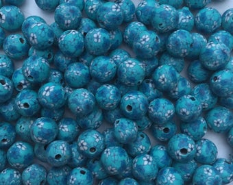 Pack of 10 x 10mm polymer clay round light blue with white coloured flower beads.