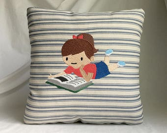 "Young girl reading 11""x 11"" pillow, embroidered on striped fabric"