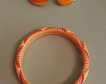 Set of orange carved plastic bracelet and orange button screw back earrings