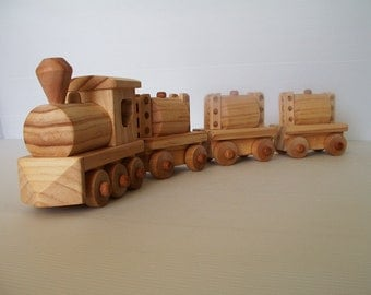 Wooden toy train with steam locomotive and three tank cars.