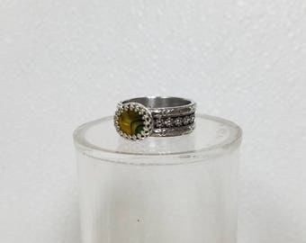 The ring is a yellow and green Paua Shell 10 mm  It is made of sterling silver size 10 3/4. this is the first ring with my new band.