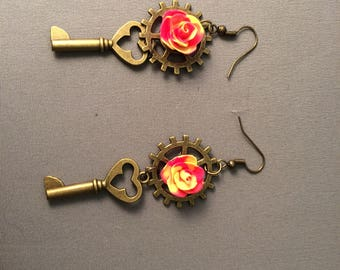 Bright yellow and pink swirl rose earrings on a steampunk gear with a key in antique gold on hook earring wires, nickel free, steampunk