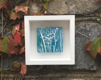 Framed original wall art, rustic clay impression of Queen Anne's Lace and mixed seed heads, blue and white in a white wooden box frame.