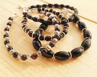 Bracelets by a thread with glossy black glass beads