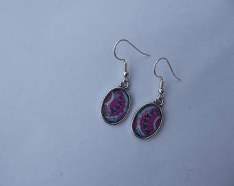 Dangling earrings with silver hooks and small glass cabochon oval purple and pink flowers on a turquoise background