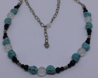 This is a black faceted beaded necklace with turquoise stone skulls and clear glow in the dark glass beads.