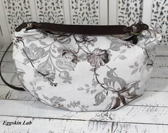 Edizione Limitata. Lilli Flowers è una borsa in cotone con base bianco sporco e fiori grigi e marroni, tracolla-manico in cuoio.