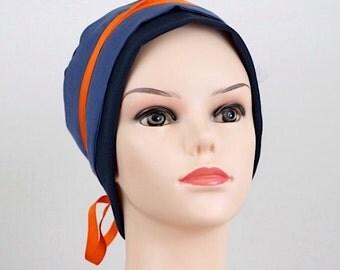 bonnet jersey bleu marine, fond tissu bleu, foulard bleu, ruban orange, tulle blanc. pièce unique.