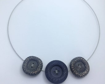 Unique necklace - three buttons mounted on a gray metal Choker