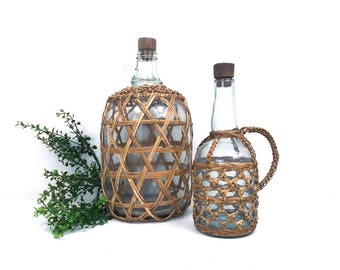 vintage 60s 70s rattan wrapped glass wine bottles pair set natural neutral boho bohemian country cottage rustic cabin decor decanter holder
