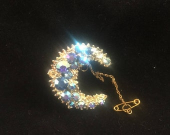 Vintage: Gold present moon brooch with blue diamante detail.