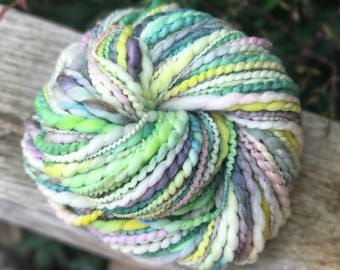 Handspun yarn, pastel colors, pale yellow, chartreuse, lavender and pale green tones, merino wool, two ply, bulky weight, bright tones