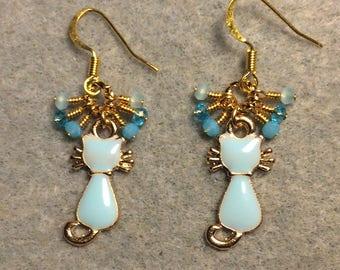 Light turquoise enamel cat silhouette charm earrings adorned with tiny dangling light turquoise Chinese crystal beads.