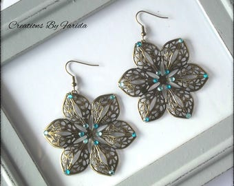 Bronze earrings dangle a flower with 6 petals with blue rhinestones and turquoise