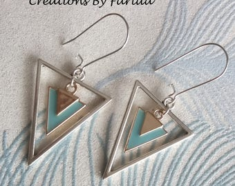 Earrings with a silver metal inverted triangle and a gold and turquoise triangle inside