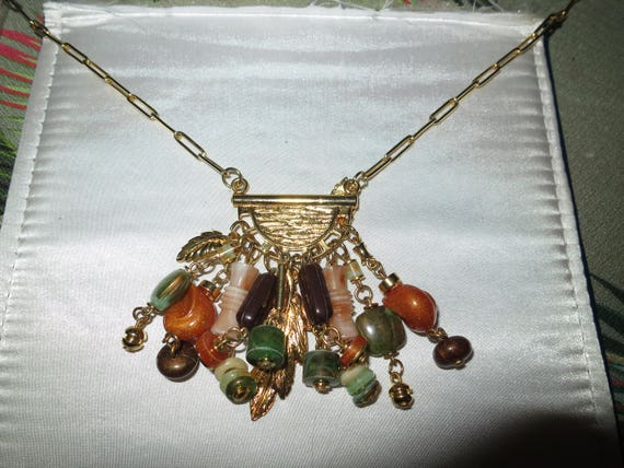 Beautiful goldtone long necklace with dangling lucite beads and leaves