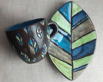 A mug with a saucer in the form of a leaf. cup ceramic.tea pair