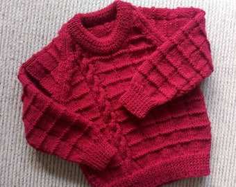 Lovely Bright Red sweater is made of eight ply and will fit a two year old warm and cosy and hand knitted