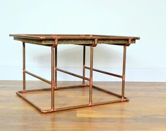Handmade by 'DISTINCTA'. Solid granite coffee / side table with a copper tube base.