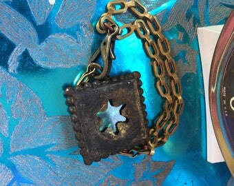 Brass bracelet with green pick and sash chain