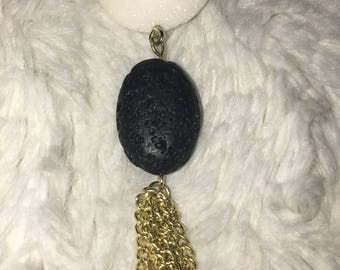 Tassle necklace with black and white stones on a gold chain