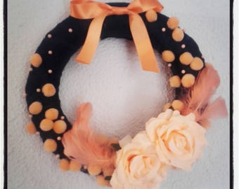Door wreath, orange flowers, feathers and tassels to hang