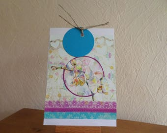 card with various collage papers and turquoise blue label
