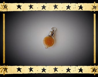 A glass Teardrop vial flattened filled with micro bead orange