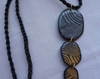Polymer clay and braided leather cord necklace.