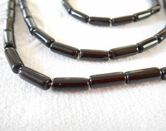 a set of 20 10 mm x 4 mm black glass tube beads.