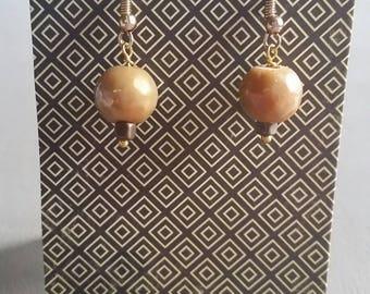 Gold tone drop earrings on gold