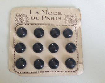 Old plate of 12 black buttons