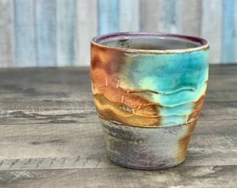 Soda-fired cup: soda fired cup, handmade cup, flashing slip, sprayed glazes. Atmospheric firing, sodafired tumbler, turquoise and orange cup