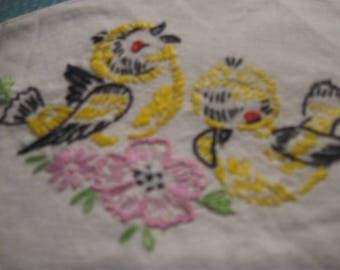 yellow birds embroidered on cotton  with stitched edge