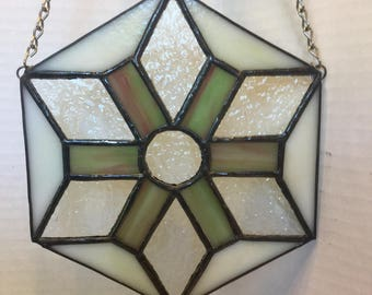 Polygon shaped stained glass window panel in greens, creams and purples