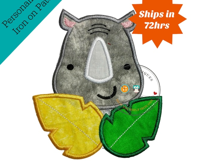Rhino iron on face in gray wash with white tusk behind a yellow leaf and green leaf: all have coordinating colored embroidery thread