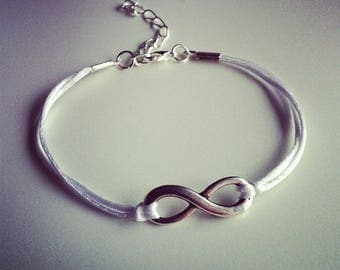 Silver infinity sign with white nylon cord bracelet