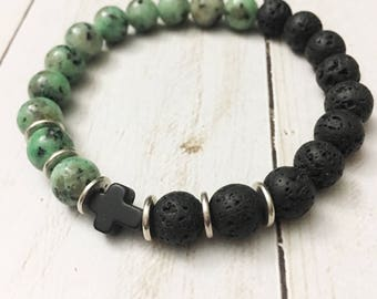 Spotted green jasper and lava stone elastic bracelet with a petite howlite cross by Jules Jewelry Box