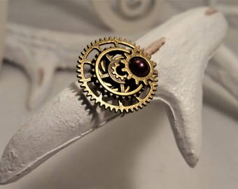 Steampunk gears and purple cabochon rings.