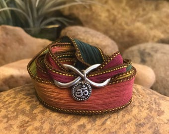 Om infinity earthy wrap bracelet with silk ribbon and charms. Great gift for yoga enthusiasts.