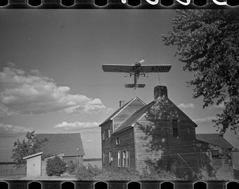 Crop Dusting plane over a barn, barnstorming, 1938, New Jersey