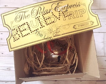 The Polar express box including themed golden ticket punched with 'believe ' a large silver bell (with red ribbon) all in a bed of raffia