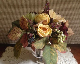 Cottage floral arrangement in a vintage silver plate pitcher.  This small floral glows with rich color and texture.
