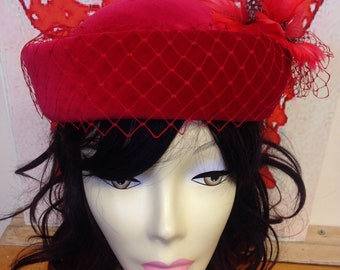 Red velvet formal hat with netting and feathers by Mitzi Lorenz