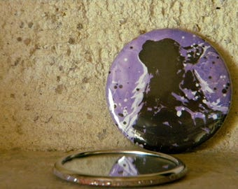 Pocket mirror of a cat in profile on purple background