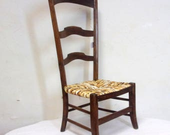 Safety early 20th century wooden chair bedded in strands of cotton fabrics in shades of off-white, Brown, Tan, rust.