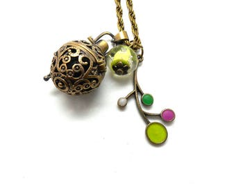 A scent! Necklace has perfume enameled flower, green bead charms and co.
