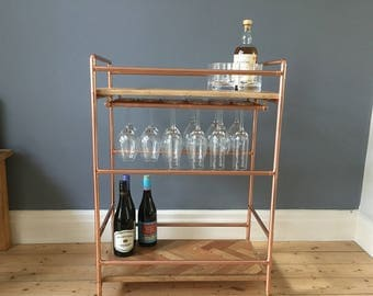 2 tier Drinks trolley with suspended wine rack in a retro industrial style with a copper pipe frame and reclaimed oak herringbone inlay